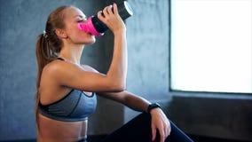 La bella ragazza nello sport copre l'acqua potabile dopo l'allenamento della palestra stock footage