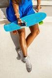 La bella ragazza nera adolescente in gonna blu si siede con il suo smartpho Fotografie Stock