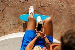 La bella ragazza nera adolescente in gonna blu si siede con il suo smartpho Immagine Stock Libera da Diritti