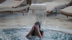 La bella ragazza nuota sotto una cascata nello stagno dell'interno stock footage