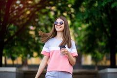 La bella ragazza in occhiali da sole cammina dalla via dell'estate con caff? immagini stock libere da diritti