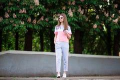 La bella ragazza in occhiali da sole cammina dalla via dell'estate con caff? fotografie stock