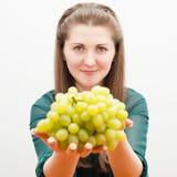 La bella ragazza offre l'uva Fotografie Stock