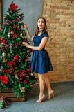 La bella ragazza orna un albero di Natale Concetto della C allegra Fotografie Stock
