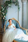 La bella ragazza in ricchi veste la menzogne sul sofà, si rilassa il concetto fotografie stock