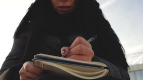 La bella ragazza scrive in capelli del taccuino si sviluppa nel vento stock footage