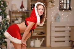 La bella ragazza sexy con capelli ricci in Santa Claus copre fotografia stock