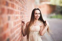 La bella ragazza sexy con forma perfetta lunga del vestito e dei capelli ha abbronzato il corpo che possing vicino alla parete Fotografia Stock