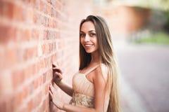 La bella ragazza sexy con forma perfetta lunga del vestito e dei capelli ha abbronzato il corpo che possing vicino alla parete Immagine Stock