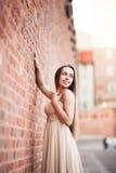 La bella ragazza sexy con forma perfetta lunga del vestito e dei capelli ha abbronzato il corpo che possing vicino alla parete Immagini Stock Libere da Diritti