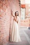 La bella ragazza sexy con forma perfetta lunga del vestito e dei capelli ha abbronzato il corpo che possing vicino alla parete Fotografia Stock Libera da Diritti