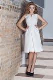 La bella ragazza sexy elegante con la bella acconciatura e la sera luminosa preparano nel vestito bianco da sera e nelle scarpe n Fotografia Stock