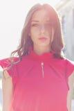 La bella ragazza sexy in un vestito rosso con un delicato esamina il sole al tramonto nel giorno soleggiato luminoso Fotografie Stock Libere da Diritti