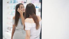 La bella ragazza si pavoneggia davanti allo specchio in deposito cosmetico, movimento lento