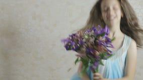 La bella ragazza si rallegra il mazzo donato dei fiori e turbina stock footage