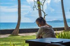 La bella ragazza si siede ed aspettando una telefonata sulla veranda il bungalow sulla spiaggia dell'oceano nell'isola Indonesia  immagine stock libera da diritti