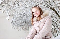 La bella ragazza si siede sopra per nevicare Immagini Stock