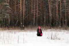 La bella ragazza si siede su neve e distoglie lo sguardo il giorno di inverno Immagine Stock