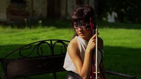La bella ragazza si siede su un banco con un violino sul bello parco stock footage