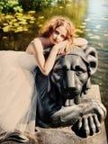La bella ragazza si siede su una statua del leone Fotografie Stock
