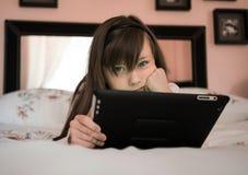 La bella ragazza si trova su un letto e gioco di computer del gioco Fotografia Stock
