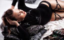 La bella ragazza si trova su una coperta bianca e sui cuscini con i modelli Immagini Stock