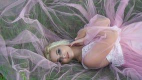 La bella ragazza si trova su uno schiarimento fra i fiori bianchi stock footage