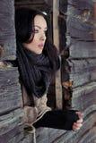 La bella ragazza sola guarda fuori la finestra della casa in un giorno di inverno gelido della radura dell'inverno Immagine Stock