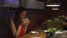 La bella ragazza sorridente in vestito rosso beve il vin brulé alla caffetteria modificato archivi video