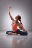 La bella ragazza sportiva degli Yogi di misura pratica l'yoga immagine stock libera da diritti