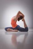 La bella ragazza sportiva degli Yogi di misura pratica l'yoga immagine stock
