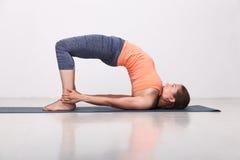 La bella ragazza sportiva degli Yogi di misura pratica l'yoga immagini stock libere da diritti