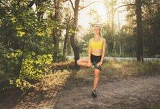 La bella ragazza sportiva mette in mostra gli esercizi in foresta Fotografie Stock Libere da Diritti