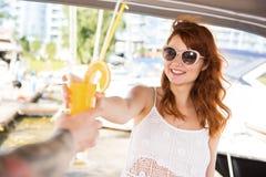 La bella ragazza sta andando bere il cocktail con gli uomini sull'yacht immagini stock