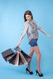La bella ragazza sta andando a fare spese con la gioia Fotografia Stock