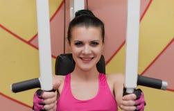 La bella ragazza sta esercitandosi nel club di forma fisica sul simulatore Immagine Stock