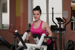 La bella ragazza sta esercitandosi nel club di forma fisica sul simulatore Immagini Stock Libere da Diritti
