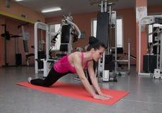 La bella ragazza sta esercitandosi nel club di forma fisica sulla coperta allungamento Fotografie Stock