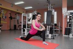La bella ragazza sta esercitandosi nel club di forma fisica sulla coperta allungamento Fotografia Stock Libera da Diritti