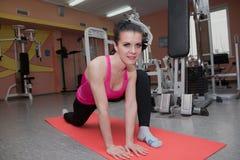 La bella ragazza sta esercitandosi nel club di forma fisica sulla coperta allungamento Fotografie Stock Libere da Diritti