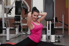 La bella ragazza sta esercitandosi nel club di forma fisica sulla coperta allungamento Immagini Stock Libere da Diritti