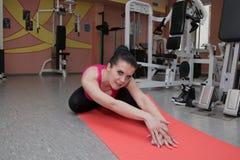 La bella ragazza sta esercitandosi nel club di forma fisica sulla coperta allungamento Immagini Stock