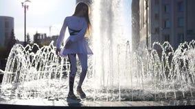 La bella ragazza sta filando stare sull'orlo della fontana e con la gioia lo salta giù HD, 1920x1080 lento video d archivio