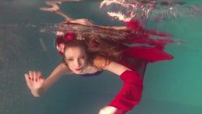 La bella ragazza sta galleggiando sotto l'acqua nello stagno Modo e bellezza video d archivio