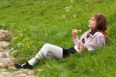 La bella ragazza sta saltando le bolle di sapone Fotografie Stock Libere da Diritti
