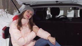 La bella ragazza sta sedendosi in automobile bianca il giorno di inverno soleggiato e sta sorridendo allegro archivi video