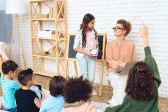 La bella ragazza sta tenendo i vetri di realtà virtuale in mani accanto all'insegnante nella classe Immagine Stock