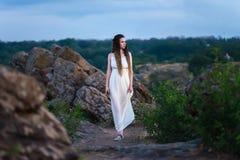 La bella ragazza stessa in vestito bianco con i dreadlocks cammina su terreno roccioso, di mattina all'alba immagine stock