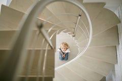 La bella ragazza teenager in jeans copre sotto le scale Immagine Stock