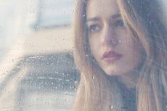 La bella ragazza triste con i grandi occhi in un cappotto è dietro vetro bagnato fotografia stock libera da diritti